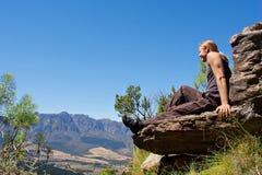 Lächelnder Bergsteiger sitzt oben auf Berg stockfoto