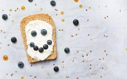 Lächelnder Blaubeertoast, Beeren-, Frischkäse-Leinsamen und Ahornsirup-Nachtisch, gesunde organische Mahlzeit lizenzfreie stockbilder
