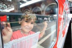 Lächelnder Blick des kleinen Mädchens vom Serienfenster lizenzfreies stockbild