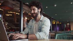 Lächelnder Blogger, der Laptop auf Tabelle im Café verwendet stock video footage