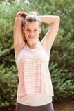Lächelnder blonder Athlet, der Arme ausdehnt Stockfotografie