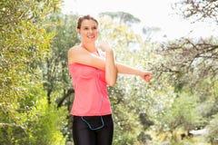 Lächelnder blonder Athlet, der Arme ausdehnt Stockfotos