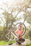 Lächelnder blonder Athlet, der ihre Mountainbike überprüft Stockfotografie