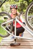 Lächelnder blonder Athlet, der ihre Mountainbike überprüft Lizenzfreies Stockbild