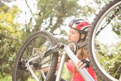 Lächelnder blonder Athlet, der ihre Mountainbike überprüft Lizenzfreie Stockfotografie