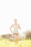 Lächelnder blonder Athlet, der im Gras rüttelt Stockbilder