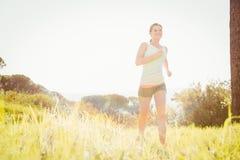Lächelnder blonder Athlet, der im Gras rüttelt Lizenzfreies Stockfoto