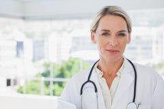 Lächelnder blonder Doktor, der ein Klemmbrett hält Lizenzfreie Stockbilder