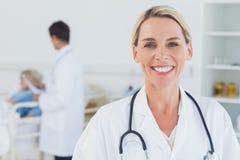 Lächelnder blonder Doktor, der mit Doktor teilnimmt an Patienten auf BAC aufwirft Stockbild