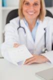 Lächelnder blonder Doktor, der Verordnungblicke gibt Lizenzfreie Stockbilder