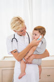 Lächelnder blonder Doktor mit Kind und Stethoskop Stockbilder