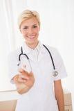 Lächelnder blonder Doktor mit Spritze und Stethoskop Stockfotografie