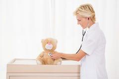 Lächelnder blonder Doktor mit Stethoskop auf dem Teddybären Stockfoto