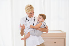Lächelnder blonder Doktor und Kind mit Stethoskop Stockbilder