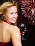 Lächelnder blonder Frauenholdingwein und Feiern Stockfotografie
