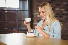 Lächelnder blonder genießender Kuchen und Kaffee Lizenzfreies Stockbild