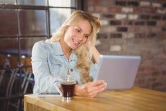 Lächelnder blonder haltener Tablet-Computer Lizenzfreie Stockbilder