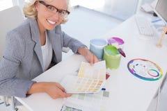Lächelnder blonder Innenarchitekt, der Farbtafeln hält Stockfoto