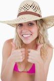 Lächelnder blonder Jugendlicher, der sich ihr zwei Daumen zeigt Stockbild