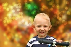 Lächelnder blonder Junge auf einem Roller Stockbild