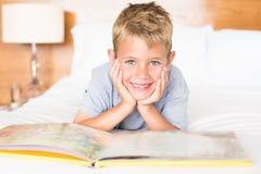 Lächelnder blonder Junge, der auf dem Bett liest ein Märchenbuch liegt Stockfoto