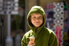 Lächelnder blonder Junge in der grünen Strickjacke mit Eiscreme Lizenzfreies Stockfoto