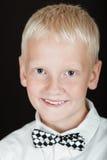 Lächelnder blonder Junge, der karierte Fliege trägt Stockbild