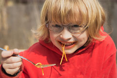 Lächelnder blonder Junge mit Gläsern isst Spaghettis Lizenzfreie Stockfotografie
