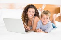 Lächelnder blonder Junge und Mutter, die auf Bett unter Verwendung des Laptops liegen Lizenzfreies Stockfoto