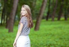 Lächelnder blonder kaukasischer Jugendlicher, der im grünen Wald aufwirft Stockfoto