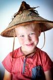 Lächelnder blonder kleiner Junge, der asiatischen Weidenhut trägt Stockbilder