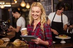 Lächelnder blonder Kunde vor dem Zähler unter Verwendung der Tablette Stockfoto