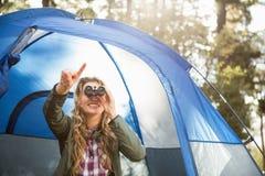 Lächelnder blonder Lagerbewohner, der durch Ferngläser schaut Stockbilder