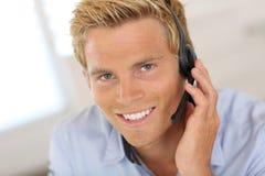 Lächelnder blonder Mann, der auf Kopfhörer spricht Stockfotografie