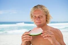 Lächelnder blonder Mann, der ein Stück einer Wassermelone anhält Lizenzfreie Stockfotos