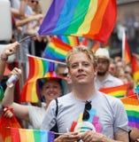 Lächelnder blonder Mann, viele von Regenbogen Pride Flaggen im backgroun Stockbild