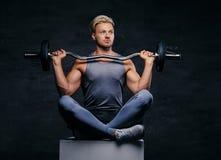 Lächelnder blonder sportlicher Mann sitzt auf einem weißen Kasten mit den gekreuzten Beinen und hält Barbell Lizenzfreie Stockbilder
