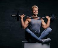 Lächelnder blonder sportlicher Mann sitzt auf einem weißen Kasten mit den gekreuzten Beinen und hält Barbell Lizenzfreies Stockfoto