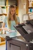 Lächelnder blonder Student, der eine Kopie erstellt Lizenzfreies Stockfoto