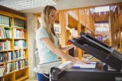Lächelnder blonder Student, der eine Kopie erstellt Lizenzfreies Stockbild