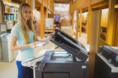 Lächelnder blonder Student, der eine Kopie erstellt Lizenzfreie Stockfotografie