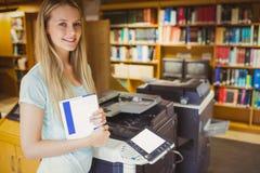 Lächelnder blonder Student, der eine Kopie erstellt Stockfotos