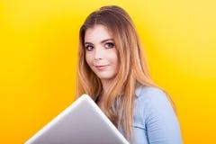 Lächelnder blonder Student, der einen Laptop in den Händen hält Stockfotos