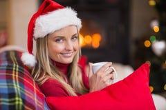 Lächelnder blonder tragender Sankt-Hut beim Halten eines Bechers Stockbild