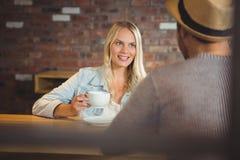 Lächelnder blonder trinkender Kaffee mit Freund Stockbild
