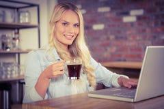 Lächelnder blonder trinkender Kaffee und Anwendung des Laptops Stockfotos