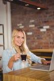Lächelnder blonder trinkender Kaffee und Anwendung des Laptops Stockbilder