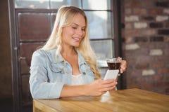 Lächelnder blonder trinkender Kaffee und Anwendung von Smartphone Lizenzfreie Stockfotografie