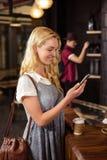 Lächelnder blonder trinkender Kaffee und Anwendung von Smartphone Stockfotografie