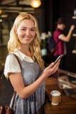 Lächelnder blonder trinkender Kaffee und Anwendung von Smartphone Lizenzfreies Stockbild